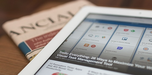 tablet laying on business newspaper